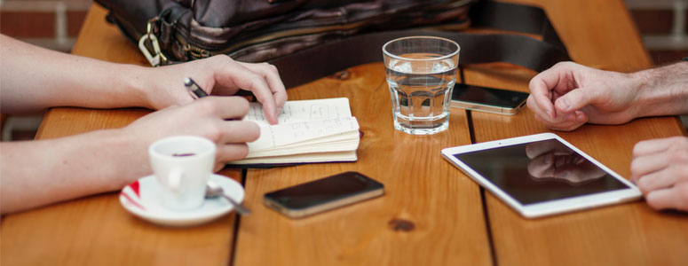 close up of a table with someone writing in a book