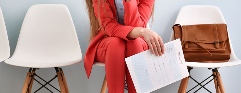 woman sitting with her cv in hand waiting to be interviewed