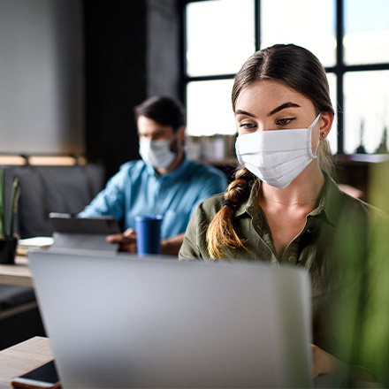 Girl with mask on sat at desk