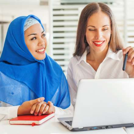 woman teaching another woman with laptop